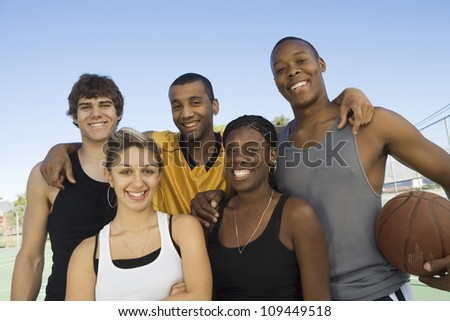 Group portrait of multiracial friends with basketball - stock photo