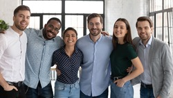 Group portrait of smiling diverse multiracial businesspeople look at camera posing in office together, happy multiethnic young colleagues hug show unity and support, teamwork, leadership concept