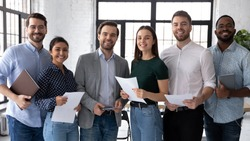 Group portrait of smiling diverse young multiethnic businesspeople posing together in modern office, happy motivated multiracial employees show unity and success, teamwork, cooperation concept