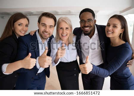 Group portrait of smiling multiracial colleagues posing in office show thumbs up recommend good service, happy diverse businesspeople give recommendation of company, acknowledgment concept Foto d'archivio ©
