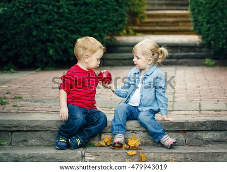 Group portrait of two white Caucasian cute adorable funny children toddlers sitting together sharing apple food, love friendship childhood concept, best friends forever