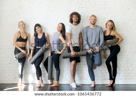Group portrait of young sporty people looking at camera. Candid students taking rest after fitness activity, time to recover strength, Fitness or yoga instructors friendly smiling, inviting for lesson #1065436772