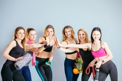 Group portrait of young sporty woman with water, fresh fruits, different equipment give high five beside grey wall laughing together. Candid funny females giving inspiration for fitness activity.
