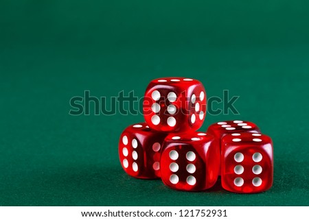 Group red dices on the green cloth.