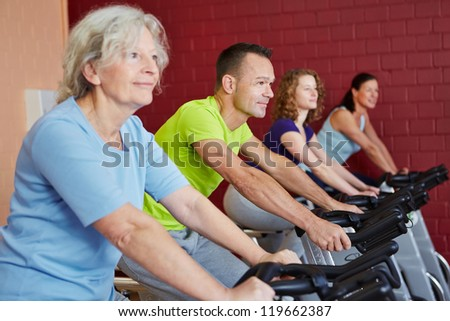 Group riding spinning bikes in a fitness class in health club