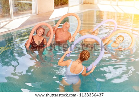 Group seniors at aquagym in the hotel pool during a wellness holiday