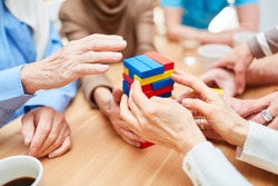 Group seniors with dementia builds a tower in the nursing home from colorful building blocks