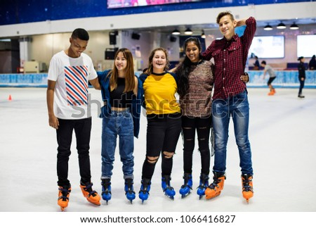 Group shot of teenage friends on the rink ice skating rink