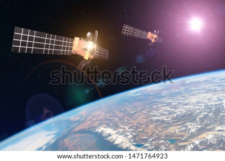 Group space satellite orbiting the earth and bright lights sun reflected from solar panels. Elements of this image furnished by NASA
