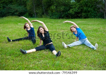 Group stretching workout - three cute girls stretches outdoors on a green grass field in park