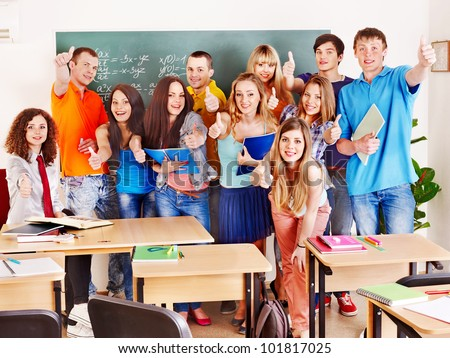 Group student near blackboard in classroom.