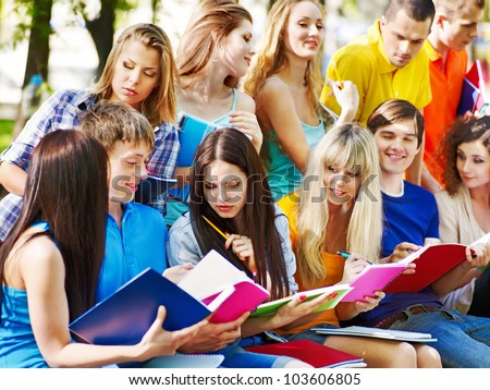 Group student with notebook on bench outdoor.