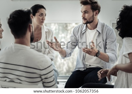 Group therapist. Nice pleasant young man looking at the group members and speaking to them while telling his story Stock foto ©