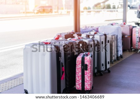 Group tour trip vacation or holiday tourism insurance concept : Large suitcases or baggage front road at hotel waiting bus tours with light flare.