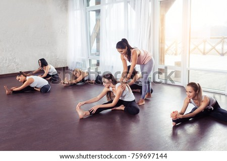Group women doing stretching and yoga exercises with instructor in fitness class against window