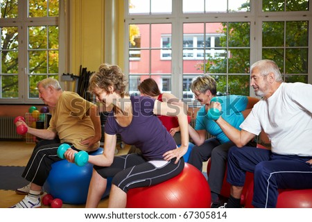 Group working out with dumbbells in gym