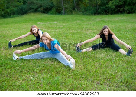 Group workout - Three girls work out in nature and stretches muscles on green grass field in park