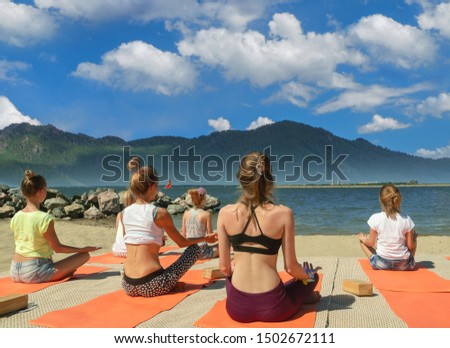 Group yoga class by the sea. Pose of relaxation and relaxation.