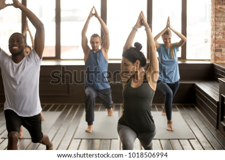 Group yoga in studio concept, diverse multiracial sporty fit people beginners practicing training with instructor teacher standing together trying to repeat warrior 1 pose, funny working out class