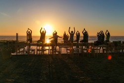Group yoga on the beach at sunset