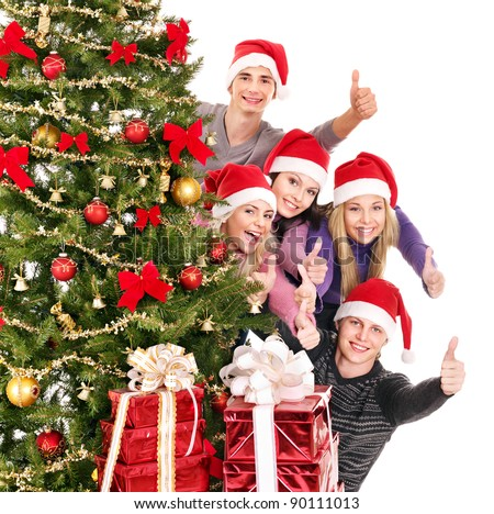 Group young people in Santa hat showing thumb up by Christmas tree..