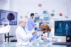 Groupe of researchers in pharmacology in a hospital laboratory. Modern equipment in research laboratory.