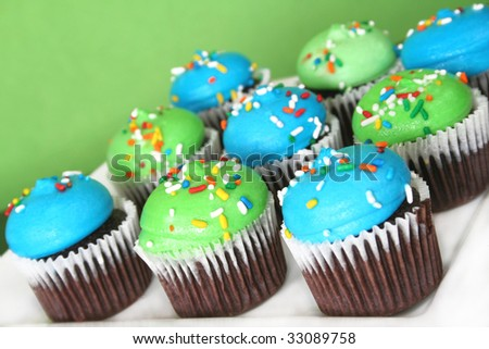 Grouping of chocolate cupcakes with blue and green frosting with colorful sprinkles.  Shot at an angle with a shallow depth of field and a selective focus.
