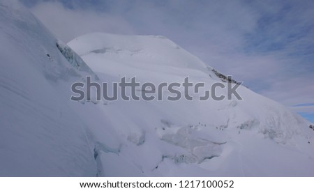 groups of backcountry skiers climbing a steep glacier with many crevasses on their way to a high alpine peak in the Bernina mountains near Pontresina in the Swiss Alps in deep winter #1217100052