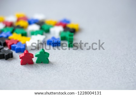 Groups of colorful meeples isolated on gray background. Blue, red, black, green and yellow. Small figures of man. Board games concept. Couple of leaders of community. Business strategy. #1228004131