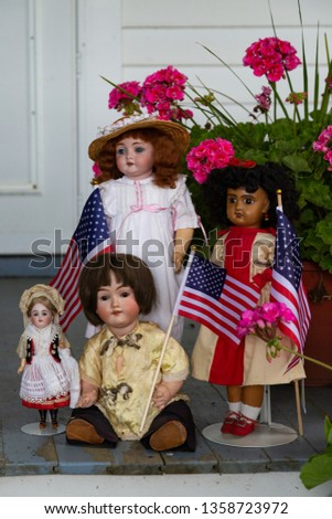 Groups of ethnically diverse dolls holding American flags waiting on the porch for the 4th of July parade to pass by.