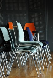 Groups of metal chairs are stacked in meeting room