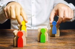 Groups of multicolored wooden people and businessman. The concept of market segmentation. Target audience, customer care. Market group of buyers. Customer relationship management. Selective focus