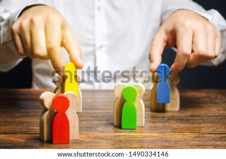 Groups of multicolored wooden people and businessman. The concept of market segmentation. Target audience, customer care. Market group of buyers. Customer relationship management. Selective focus Foto stock ©