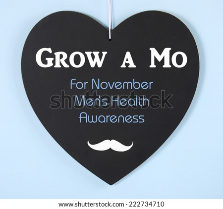 Grow a Mustache message on heart shaped blackboard for November Mens Health Issues Awareness
