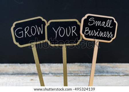 GROW YOUR SMALL BUSINESS message written with chalk on wooden mini blackboard labels, defocused chalkboard and wood table in background #495324139
