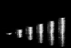 Growing money graph on a row of coin and pile of baht coins stack  isolated on black background. Finance business.