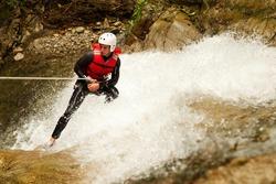 grown male wear waterproof training descending a waterfall
