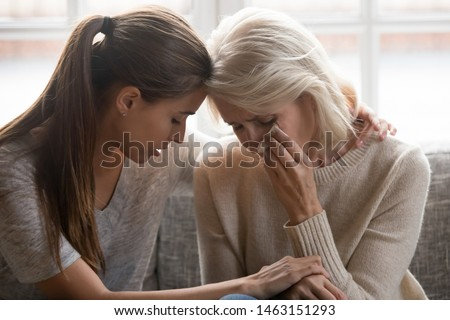 Grown up daughter soothe aged mother holds her hand feel empathy give her moral support elderly woman crying wipe tears with tissue, health problem disease, divorce broken heart adult child supporting