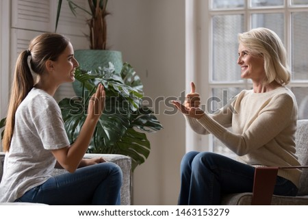 Grown up daughter talk with middle aged mother people using sign language, family sitting on armchair side view, teacher teach teenager deaf-mute girl to visual-manual gestures symbols concept image