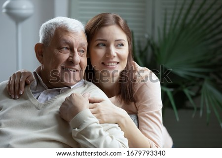 Grown up loving attentive caring granddaughter hugging elderly 75s grandfather. Young adult daughter embracing aged father looking at distance in cozy living room. Concept of family ties love and care