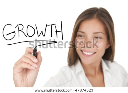 Growth and success in business concept. Young beautiful businesswoman with pen writing growth on whiteboard. Focus on black marker. Mixed race Chinese / Caucasian model isolated on white background - stock photo