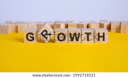 growth word written on wood block, yellow background