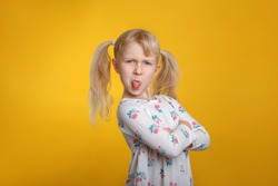 Grumpy angry Caucasian blonde girl with blue eyes in white dress posing in studio on yellow background with arms crossed on chest. Kid child expressing negative emotion showing tongue