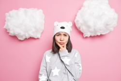 Grumpy displeased brunette young Asian woman holds chin and looks offended at camera feels angry awakes in bad mood dressed in slumber suit soft hat with bear ears isolated over pink background