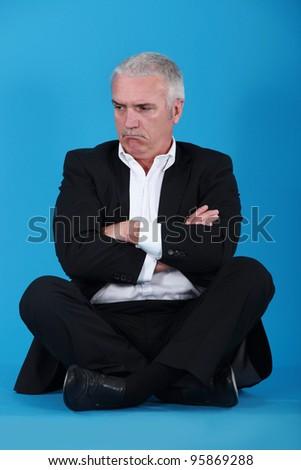Grumpy man sitting on the floor