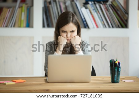 Grumpy not amused office worker looking at laptop screen in office. Young business lady bored with mundane workflow, tired from working too much. Casual businesswoman not happy with boring work task.
