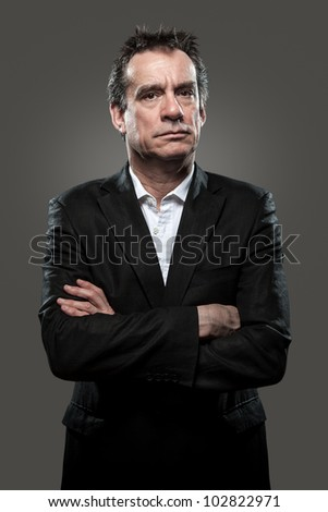 Grumpy Stern Middle Age Business Man in Suit Arms Folded Grey Background High Contrast Grunge Look