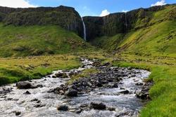 Grundarfoss Waterfall cascading down a high cliff and the Grundara River flowing through verdant grassy fields, Summer, Grundarfjordur,  Snaefellsnes Peninsula, West Iceland, Europe