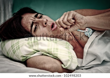 Grunge and gritty portrait of sick woman laying in bed and coughing