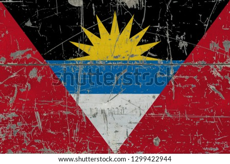 Grunge Antigua and Barbuda flag on old scratched wooden surface. National vintage background.